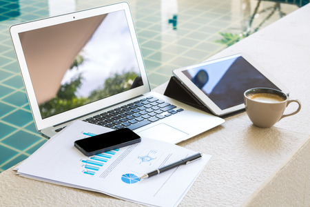 vacations: Laptop, tablet , smartphone and coffee cup with financial documents at swimming pool Stock Photo