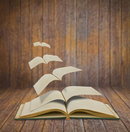 Otwarte latające stare książki w pokoju drewna
