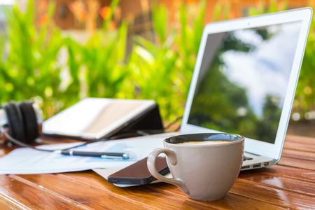 Laptop, tablet, smartphone en koffiekop met financiële documenten op houten tafel