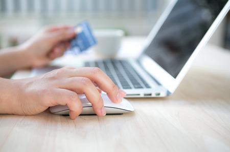 クレジット カードを保持していると、オンライン ショッピングのためのラップトップ コンピューターを使用しての手