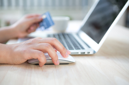 sell online: Hands holding a credit card and using laptop computer for online shopping Stock Photo