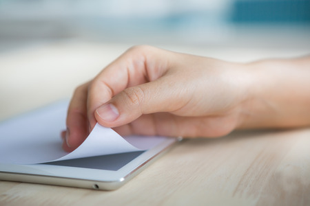 Hand open tablet with Paper Corner Fold photo