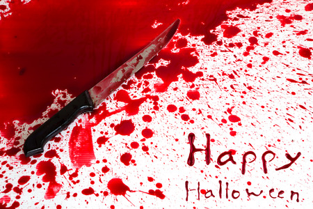 blade cut: Halloween concept : Bloody knife with blood splatter