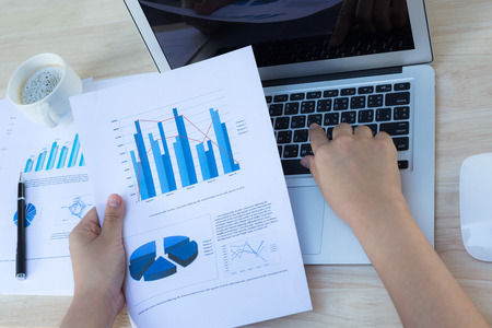 Close-up of business person use laptop with financial diagram photo