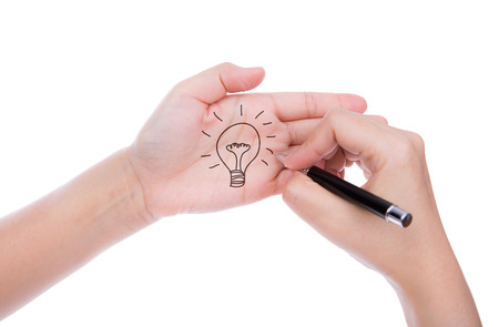 Hand with pen write idea light bulb  isolated on white background photo
