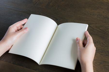 libro abierto: Manos libro abierto sobre la mesa de madera