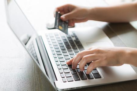 orden de compra: Manos que sostienen una tarjeta de crédito y el uso de ordenador portátil para compras en línea