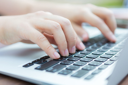 Closeup of business woman hand typing on laptop keyboard photo