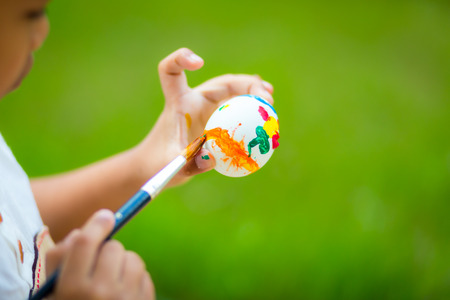 unrecognizable: Child painting easter egg with paintbrush