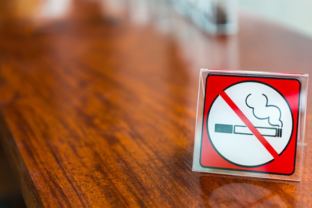 dint: No smoking sign displayed on a wooden table