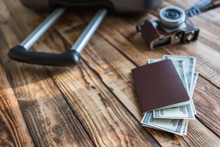 Blank passport and camera with US dollars on wood table