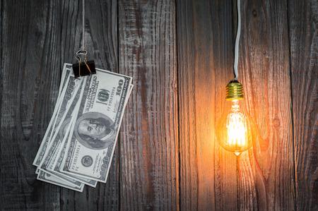 pagando: bombilla y el dólar cuelgan en el fondo de madera