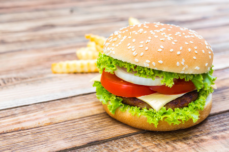 comida rapida: Hamburguesa en la mesa de madera, efecto de filtro solar flare
