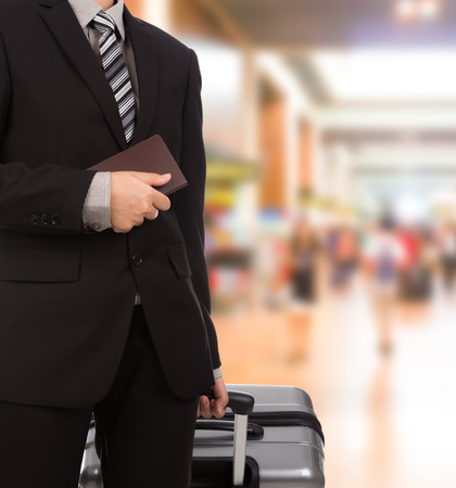 passport background: Business traveling pulling suitcase and holding passport Stock Photo
