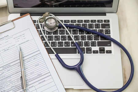 Stethoscope and prescription on laptop Stockfoto