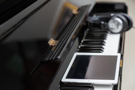 piano closeup: Tablet and head phones on Piano keys