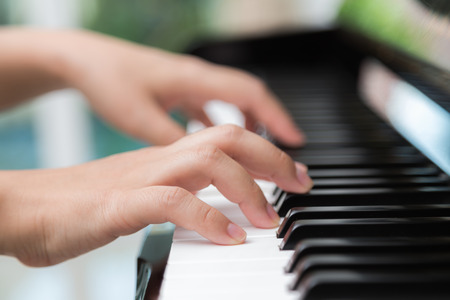 Close up of woman hands playing piano photo