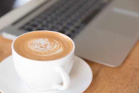 netbooks: laptop with coffee cup on old wooden table Stock Photo