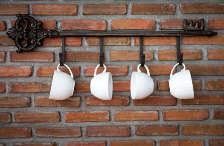 taza: Las tazas de caf� colgando de ganchos delante de la pared de ladrillo