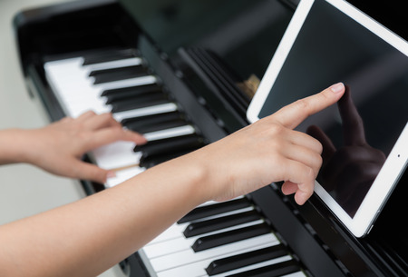 electronic piano: Woman hand use tablet and  playing piano music