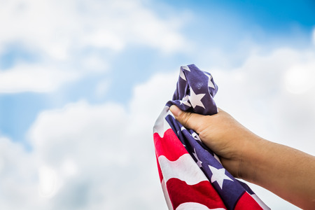 raise the white flag: American flag with stars and stripes hold with hands against blue sky Stock Photo