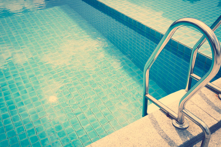 hotel with pool: Swimming pool with stairs ( Filtered image processed vintage effect. )