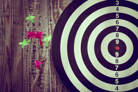 dart on target: Dartboard on wood wall (miss darts) Stock Photo