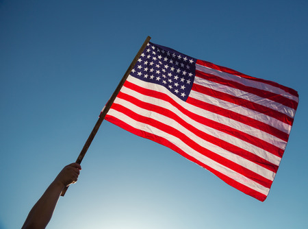 summer day: American flag with stars and stripes hold with hands against blue sky Stock Photo