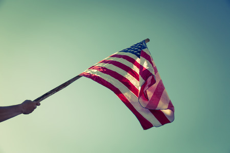 processed: American flag with stars and stripes hold with hands against blue sky ( Filtered image processed vintage effect. )
