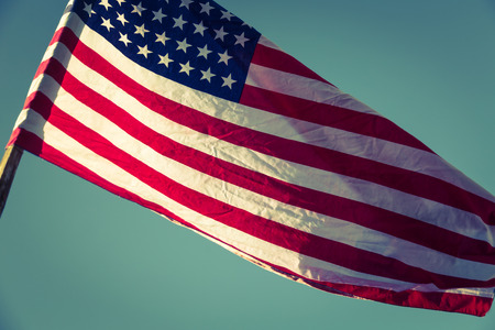 filtered: American flag over blue sky ( Filtered image processed vintage effect. )