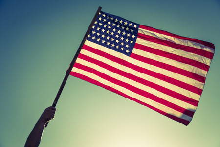 full day: American flag with stars and stripes hold with hands against blue sky ( Filtered image processed vintage effect. )