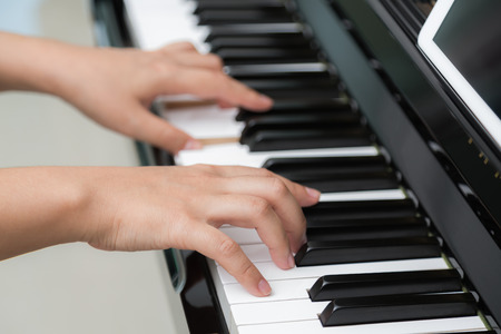 piano closeup: Close up of woman hands  playing piano Stock Photo