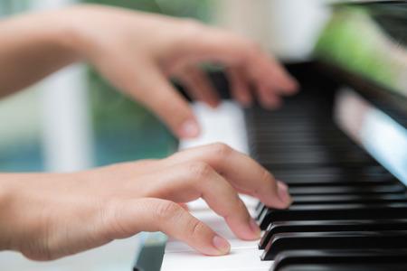 piano: Close up de manos de la mujer tocando el piano