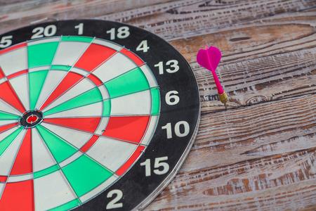 dartboard: Dartboard on wood wall (miss darts) Stock Photo