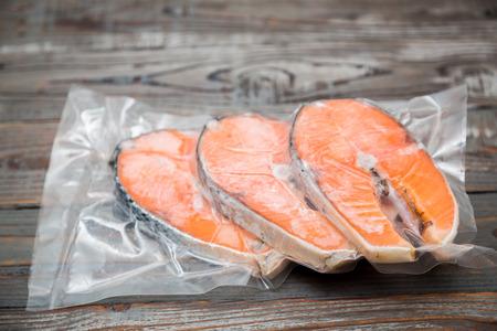 진공 패키지 나무 테이블에 냉동 연어 필레 스톡 콘텐츠