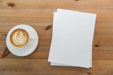 Puste katalogi, czasopisma, książki mock up na tle drewna z filiżanką kawy