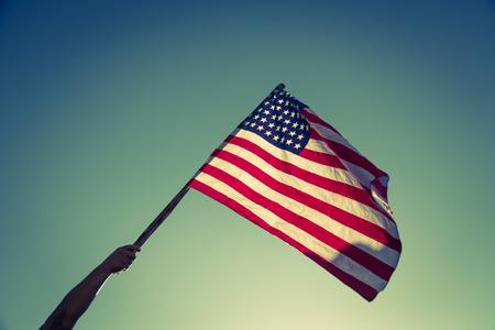 Amerikanische Flagge mit Sternen und Streifen zu halten mit den Händen gegen den blauen Himmel (gefilterte Bild verarbeitet Vintage-Effekt.)
