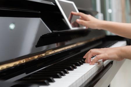 fortepian: Kobieta wykorzystanie ręka tabletka i odtwarzanie muzyki fortepianowej Zdjęcie Seryjne