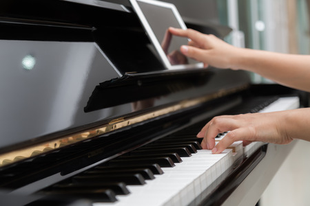 piano closeup: Woman hand use tablet and  playing piano music