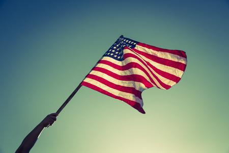 bandera estados unidos: Bandera americana con las barras y estrellas sostenga con las manos contra el cielo azul (imagen filtrada procesada efecto vintage.)