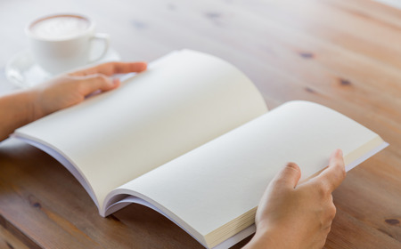 two page spread: Hands open blank catalog, magazines,book mock up on wood table with coffee