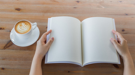 Hands open Blank catalog, magazines,book mock up on wood table with coffee 스톡 콘텐츠
