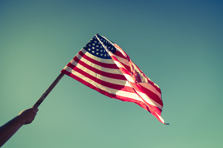 usa flag: American flag with stars and stripes hold with hands against blue sky ( Filtered image processed vintage effect. )