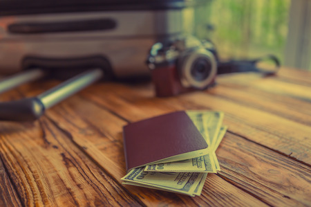 dollar sign icon: Blank passport and camera with US dollars on wood table ( Filtered image processed vintage effect. )