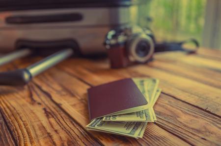 pasaporte: Pasaporte en blanco y cámara con dólares estadounidenses en la mesa de madera (imagen filtrada procesados ??efecto vintage.)