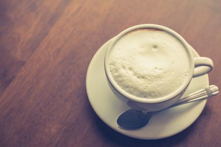 cafe latte: Hot latte art coffee on table ( Filtered image processed vintage effect. )