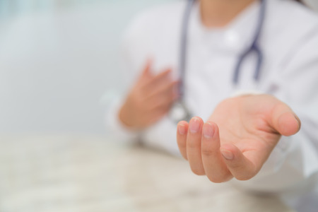 by hand: Doctor holding something in his hand