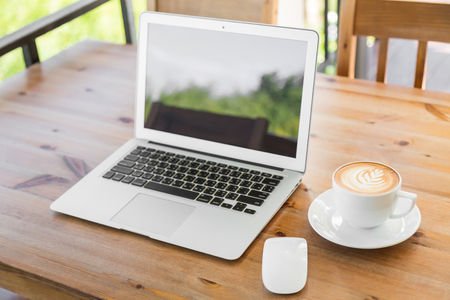 laptop with coffee cup on old wooden table Foto de archivo