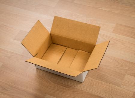 carton: Caja de cartón sobre madera