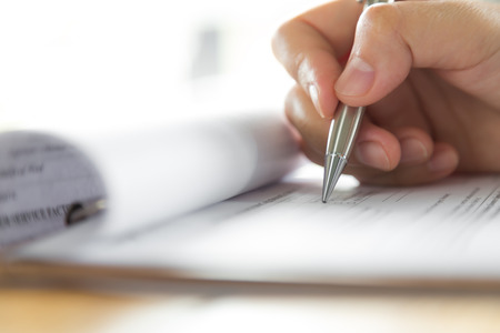 applications: Hand with pen over application form Stock Photo